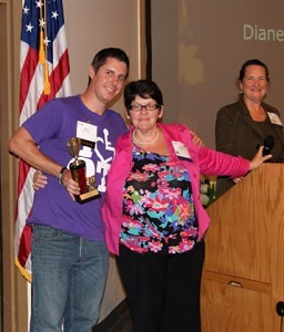 """Dr. Mary Shotwell presenting an award to Jesse Ausec  (Kelly Cosner, Joe Pickavance, Anna Leard) for developing the theme for the conference entitled """"Find your Voice""""."""