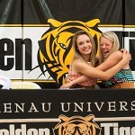 Lauren Smith, left, recieves a giant hug from her best friend and fellow golfer Taylor Young after Smith signed her golf scholarship with Brenau University.