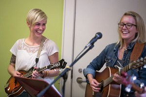 From left, Jordan Wallace, a biology senior at Brenau, laughs along side her bandmate Carly Burruss, a student at Kennesaw State University, as they play with their band, The Sawnee Mountain Train Wreck, during the Bluegrass and Books event at the Brenau University Tea Room.